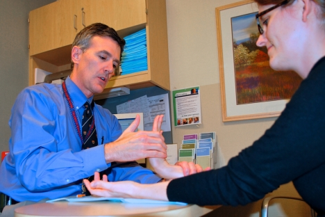 Dr David Ring examining a patient's hand at the Mass General Hospital